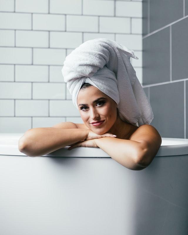 Dziewczyna w wannie z białym ręcznikiem na głowie.