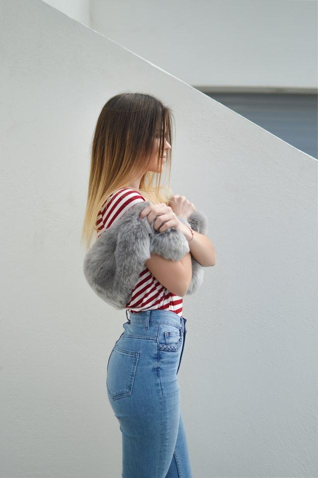 Dziewczyna stojąca bokiem z długimi włosami ombre blond.