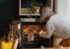Mama z córką wyjmująca potrawę z piekarnika.