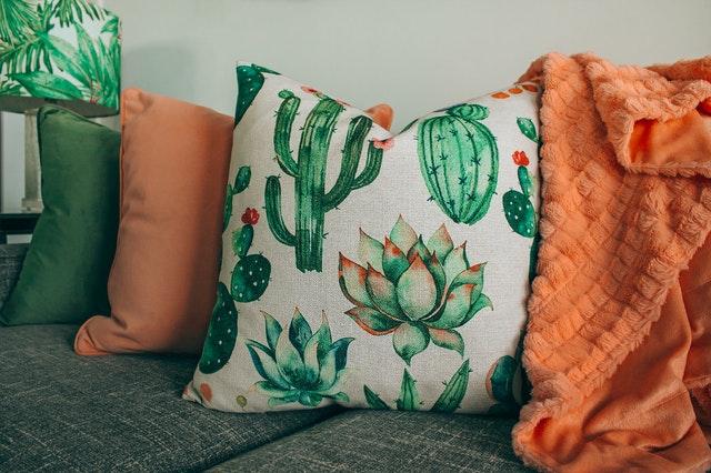 Kolorowe poduszki i pomara.ńczowa narzuta na sofę