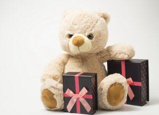 Pluszowy miś i dwa czarne prezenty z różową wstążką.