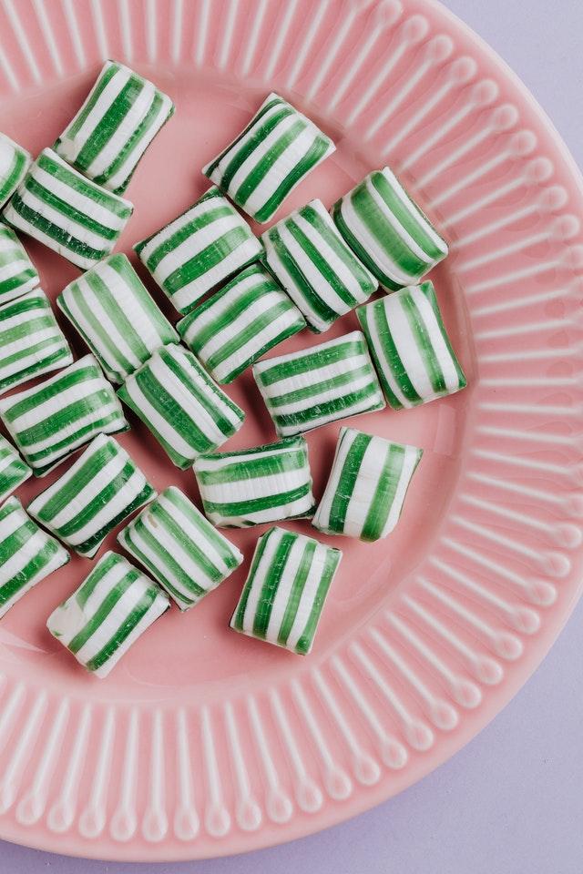 Zielone cukierki na różowym talerzu.