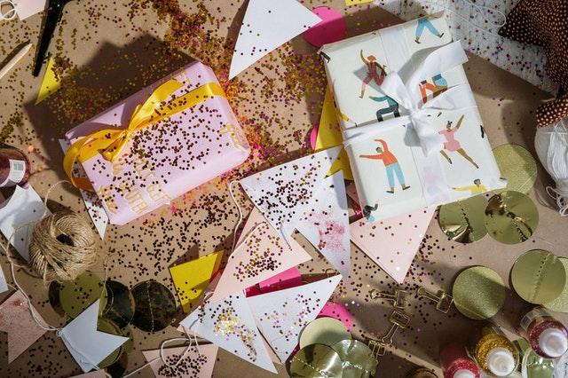 Kolorowe kartki i papier do pakowania prezentów obsypane brokatem.