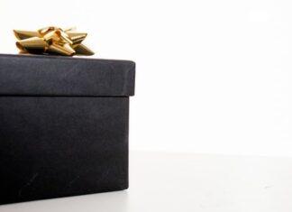 Czarny prezent ze złotą kokardką na białym tle.