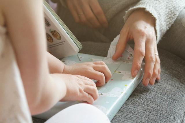 Małe dziecięce rączki ropakowujące prezent.