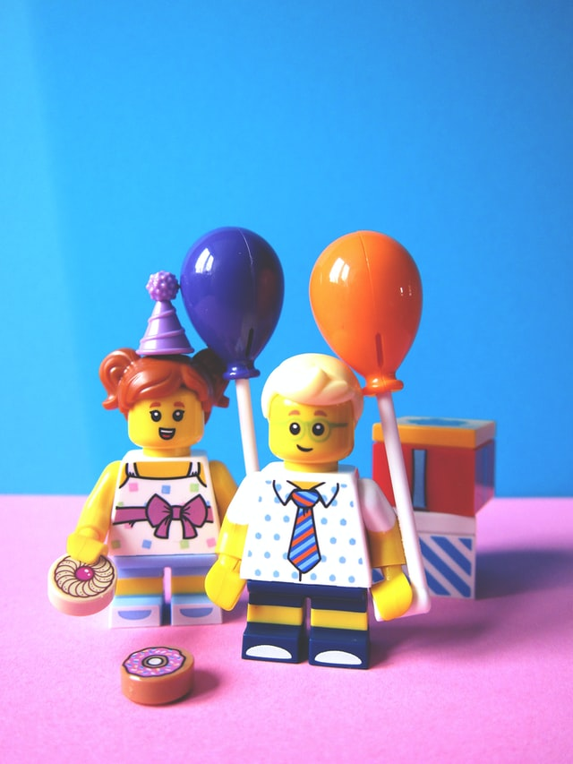 Dwa ludziki lego z balonami - chłopiec i dziewczynka.