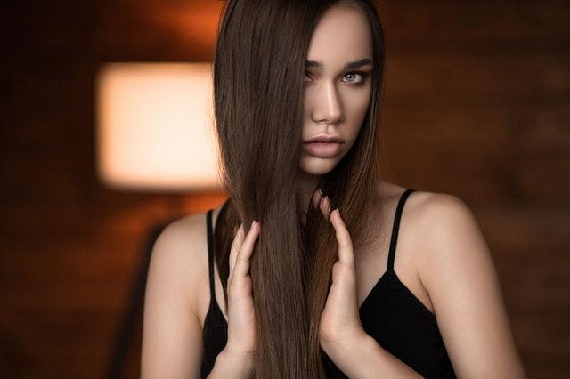 Portret dziewczyny z długimi, prostymi, ciemnymi włosami.
