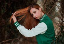 Rudowłosa dziewczyna bawi się swoimi długimi, prostymi włosami.