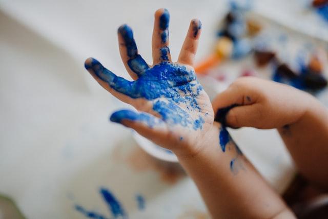 Mała dziecięca raczka ubrudzona niebieską farbą.