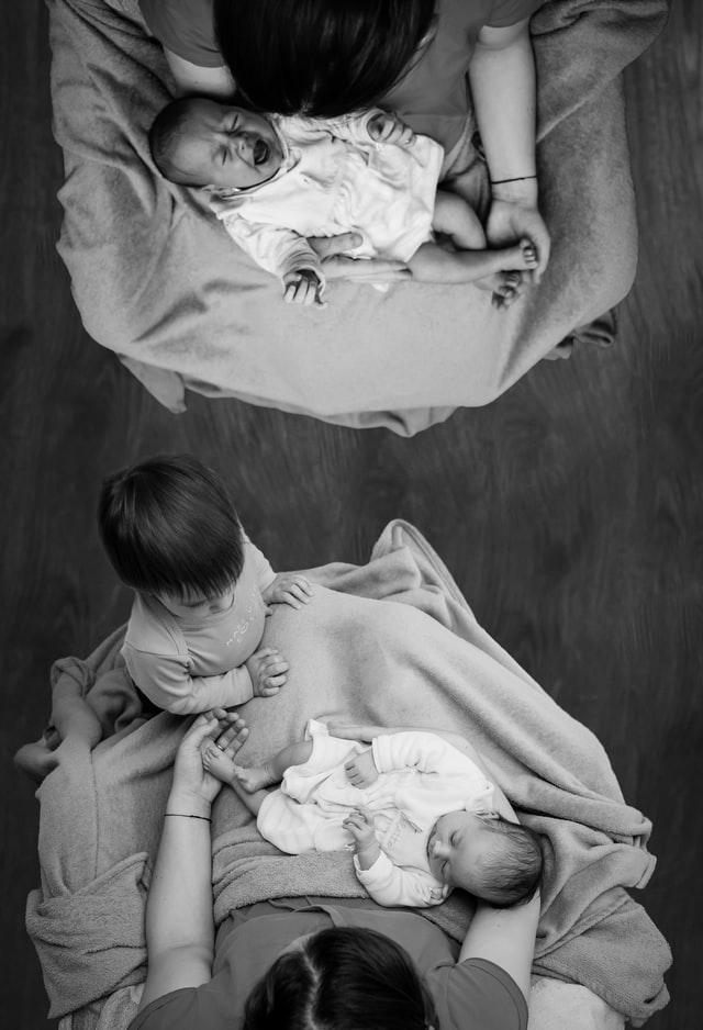 Zdjęcie rodziny z trójką dzieci. Najmłodszy noworodek płacze na kolanach mamy.