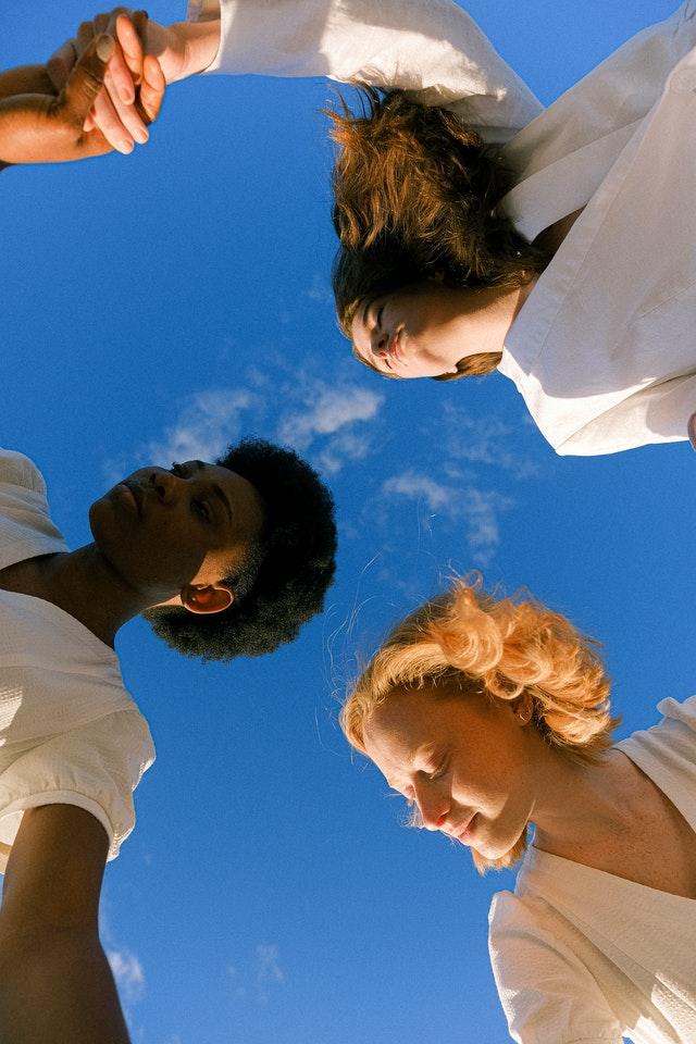 3 dziewczyny o różnej skórze i kolorze włosów, oświetlone promieniami słonecznymi.