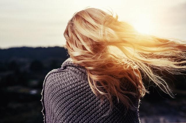 Dziewczyna o długich, blond, włosach, stojąca tyłem w promieniach słońca.