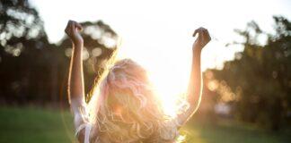 Dziewczyna stojąca tyłem w promieniach słońca i unosząca ręce do góry.