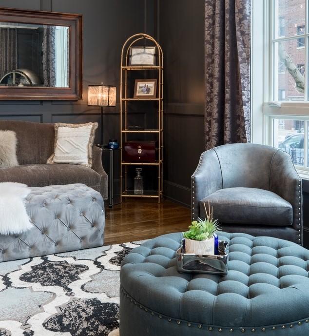 Salon z ciemnymi ścianami i skórzanym fotelem oraz pikowanym stolikiem kawowym i podnóżkiem.