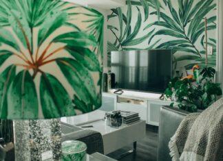 Salon z tapetą w zielone liście. Kanapa, stolik i telewizor.