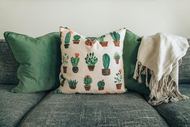 Zielona kanapa z ozdobnymi zielonymi poduszkami w kaktusy.