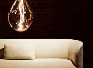 kremowa sofa na czarnym tle i lampka w kształcie żarówki