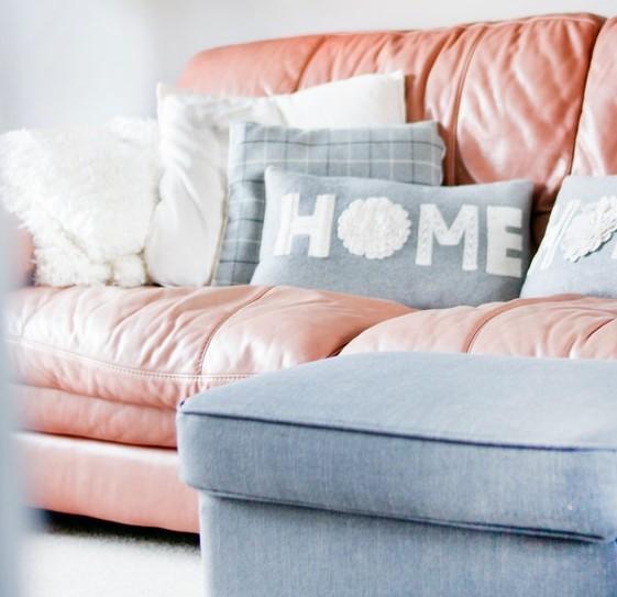 różowa, skórzana sofa z ozdobnymi, szarymi, poduszkami.