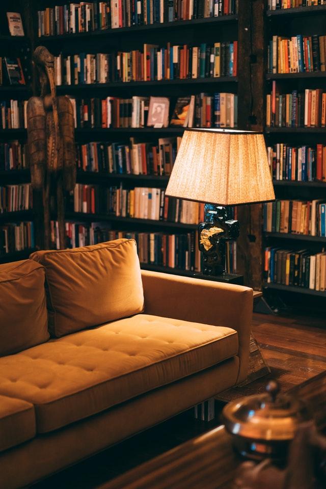 Żółtasofa z lampką na tle regału z książkami.