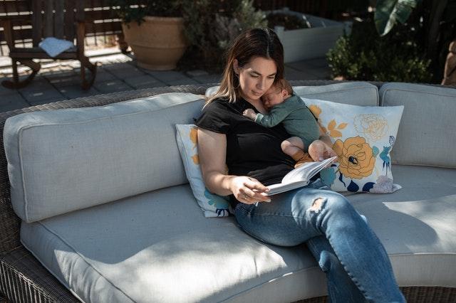 Mama siedząca na kanapie z noworodkiem i czytająca książkę