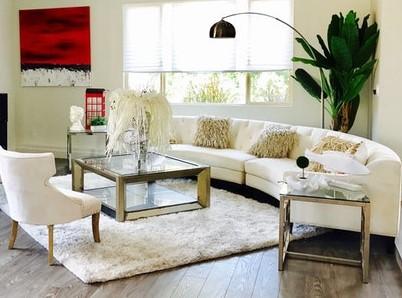 Salon z kwadratowym, szklanym stolikiem i kremową sofą i fotelem.