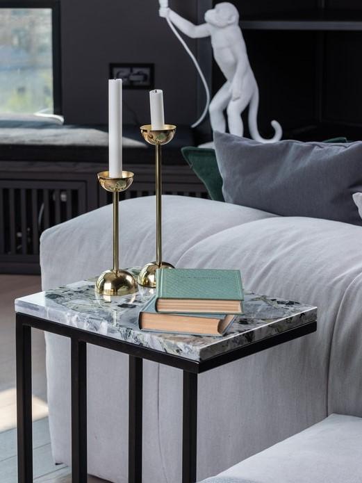 Kamienny stolik boczny przy sofie, a na nim dwie książki i dwie świece.