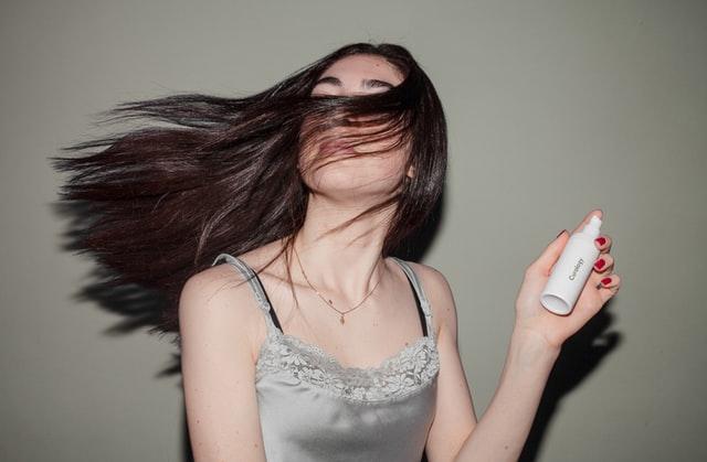 Dziewczyna z długimi ciemnymi włosami spryskuje swoje włosy sprayem do stylizacji.
