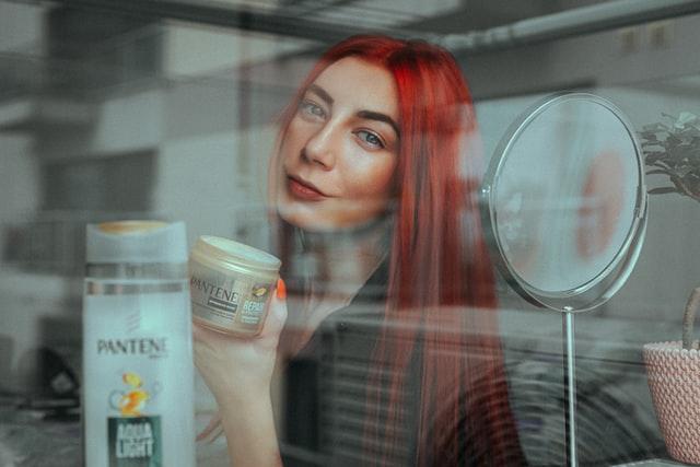 Dziewczyna z czerwonymi włosami trzymająca w ręce szampon i odżywkę.