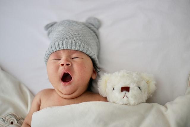 Ziewający noworodek w łóżku z białym misiem