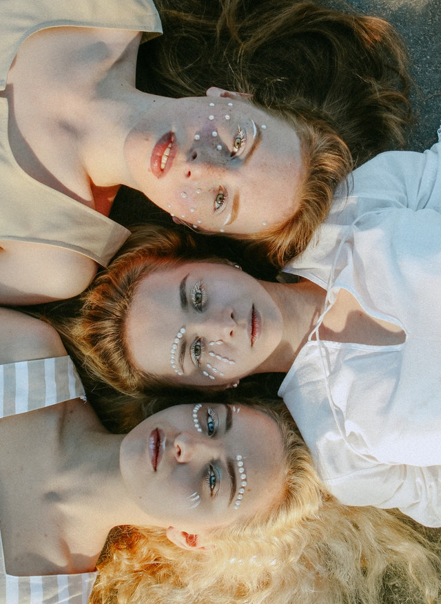 3 dziewczyny leżące obok siebie.