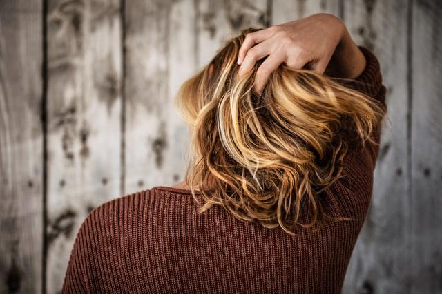 Dziewczyna stojąca tyłem i bawiąca się swoimi krótkimi blond włosami.