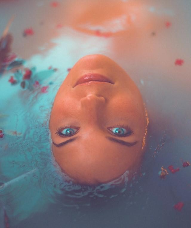 Dziewczyn zanurzona w wodzie tak, że widać tylko twarz.
