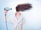 Dziewczyna susząca włosy suszarką.