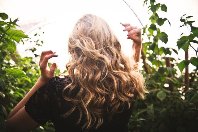 Dziewczyna stojąca tyłem z długimi, falowanymi, blond włosami.