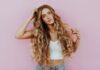 Dziewczyna z długimi,blond, kręconymi, włosami, drapiąca się po głowie.