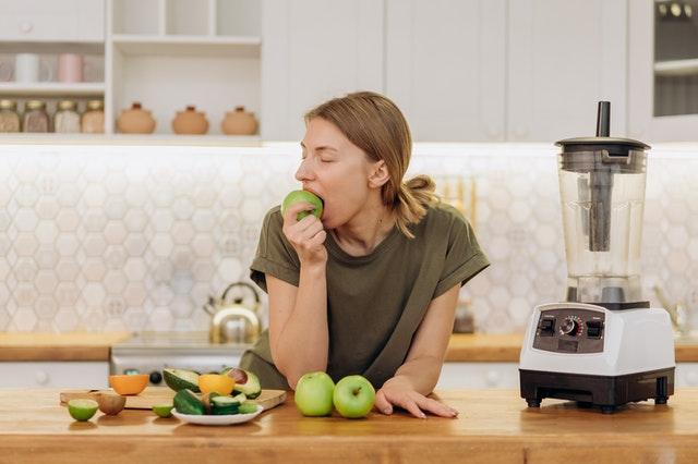 Dziewczyna w kuchni jedząca zielone jabłko.