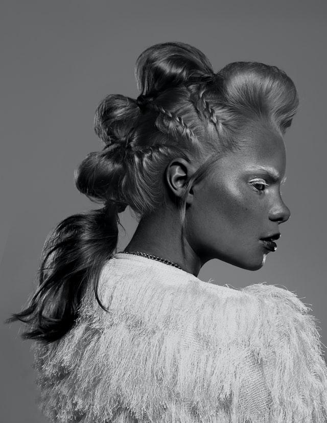 Czarno białe zdjęcie dziewczyny w ekstrawaganckiej fryzurze i makijażu.