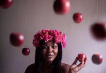 Portret ciemnoskórej dziewczyny z wiankiem z różowych kwiatów na głowie i jabłkiem w ręce. Jabłka w tle.