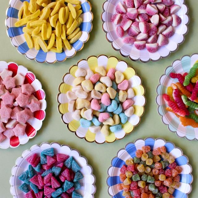 Różne, kolorowe, żelki na talerzach.